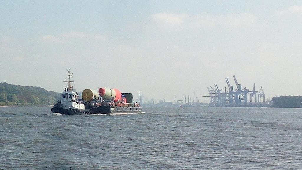 En bogserbåt på floden Elbe framför en hamn.