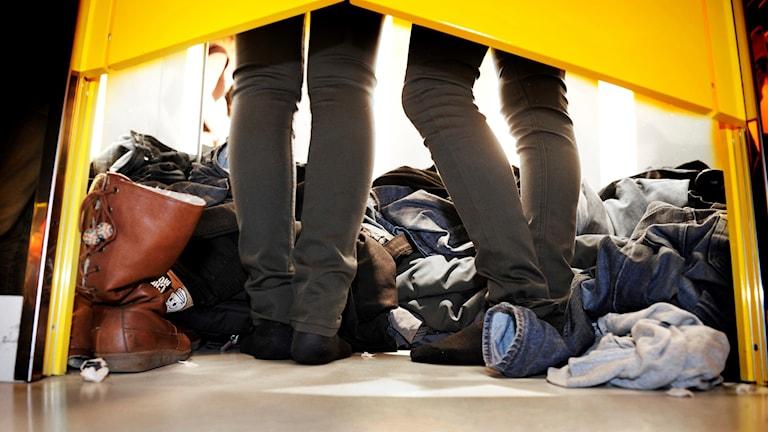 ben syns under provhyttsdörr. På golvet ligger högar med kläder.