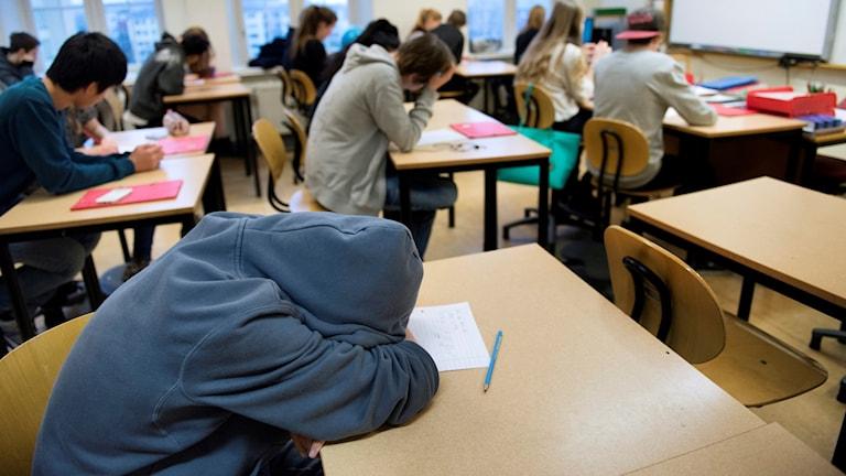 Elev som sover på skolbänken i ett klassrum.