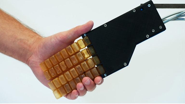 Robotens hand hälsar på en människa