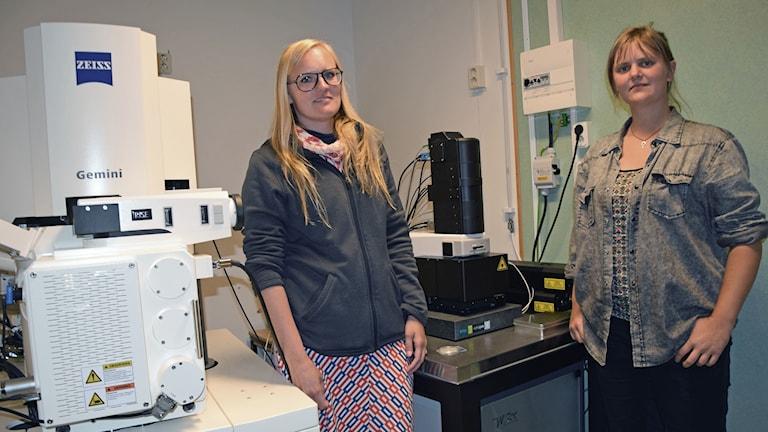 Karin Mattsson och Therese Karlsson bredvid ett mikroskop