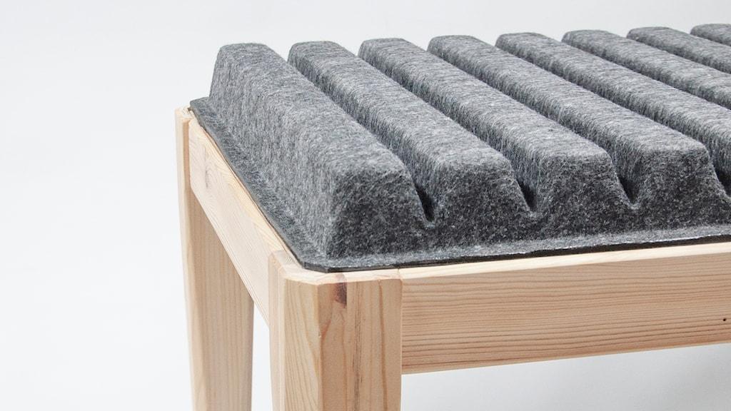 En bänk i ljust trä, med en lite annorlunda sittdyna i formgiven textilfiber.