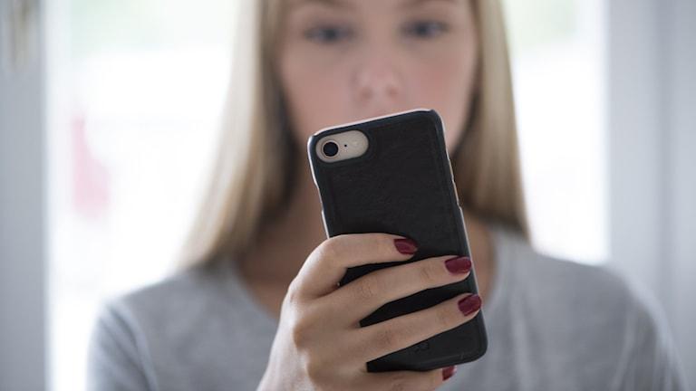 En ung tjej kollar på sin mobiltelefon.