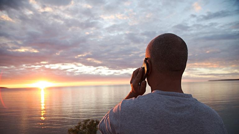 En man pratar i mobiltelefon samtidigt som han blickar ut över en solnedgång över vatten.