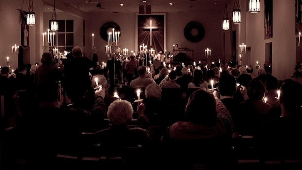 En församling fotograferad bakifrån, framåt i kyrkan. Männsikorna håller upp levande ljus mot taket. Bilden är svartvit.