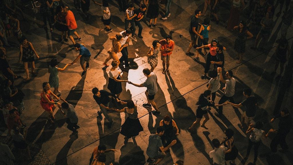 Människor dansar två och två på en upplyst gata.
