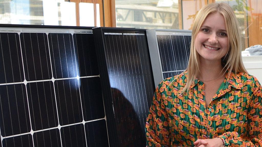 Lisanne Brummelhuis på solcellsföretaget Sungevity i Amsterdam står framför några svarta solpaneler