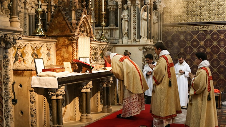 Tre präster vid ett altare.