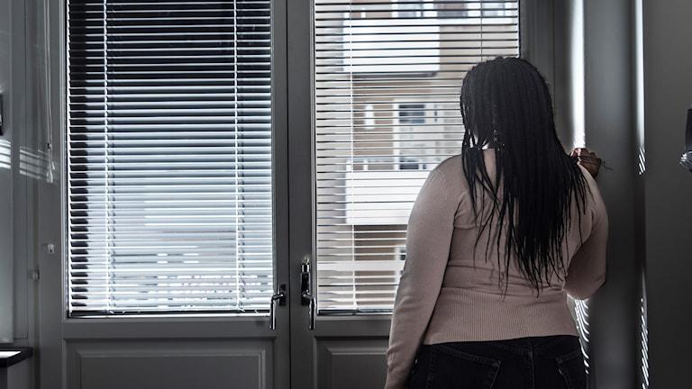 Kvinna står och tittar ut genom ett fönster.