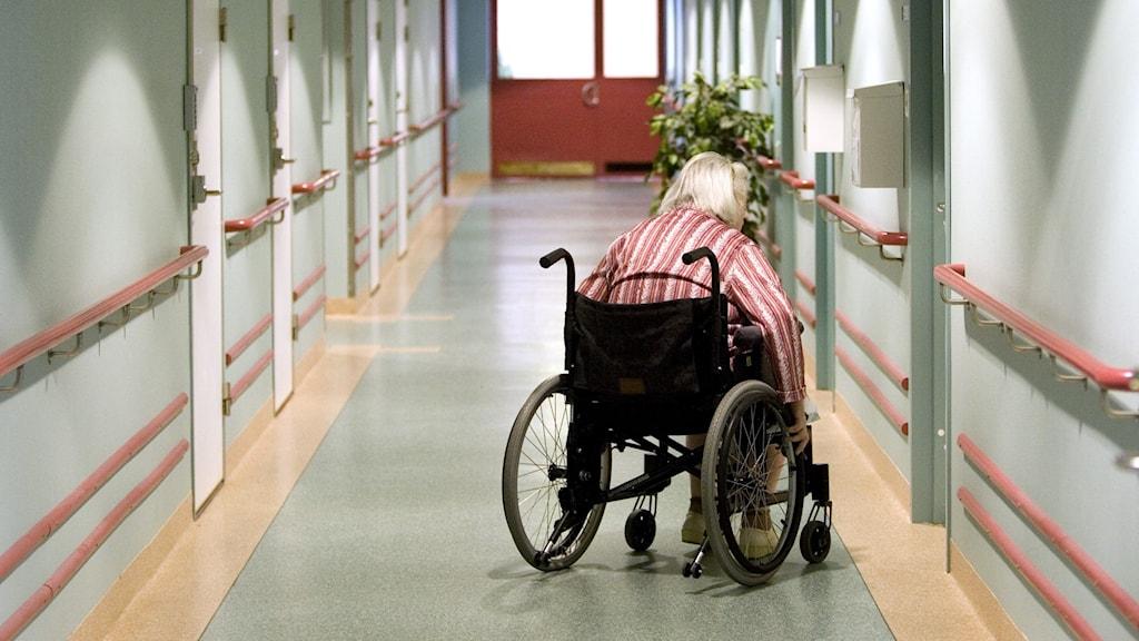 Person i rullstol i en korridor.