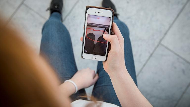 En ung kvinna ses bakifrån. Hon håller en mobil i ena handen.