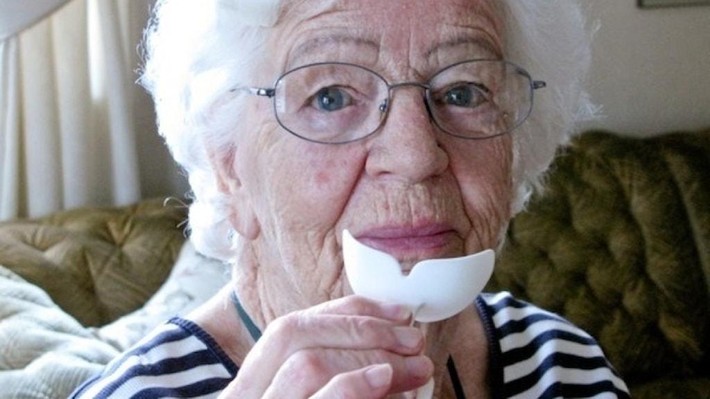 En dam håller en munskärm i handen. Ett litet plastverktyg som man kan träna upp sin sväljförmåga med.