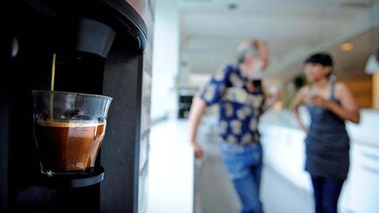 Två personer står och pratar vid en kaffeautomat