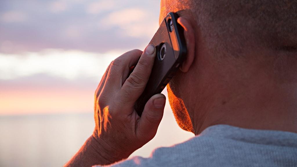 En man talar i mobiltelefon.