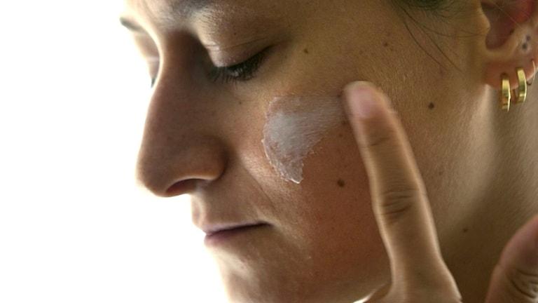 en kvinna smörjer hudkräm på sin kind