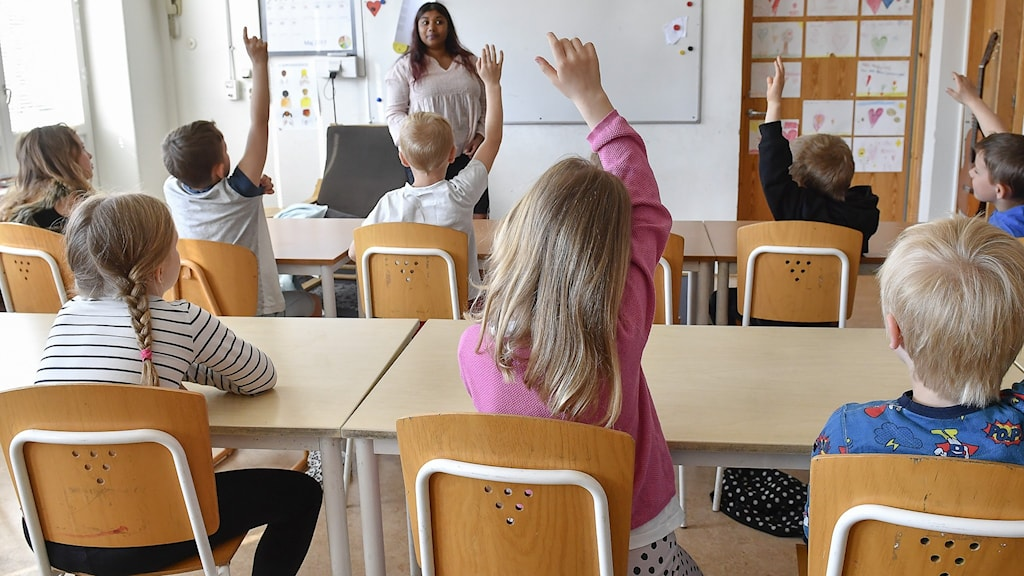 Elever och lärare i klassrum.