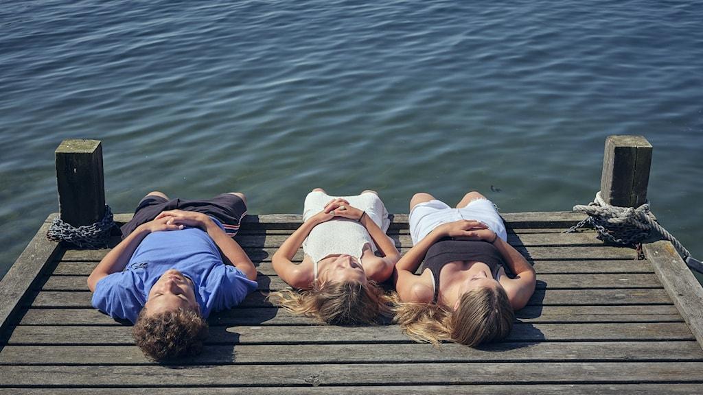 Ungdomar ligger och solar på en brygga.