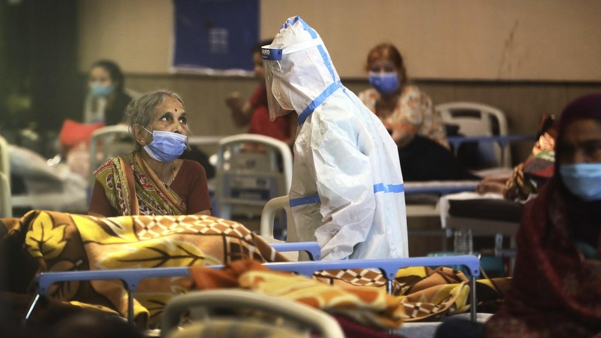 en kvinna i en sjukhussäng och en sjukhuspersonal i skyddskläder.