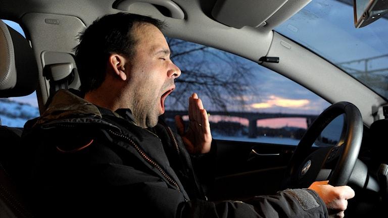 Bilförare som gäspar framför ratten