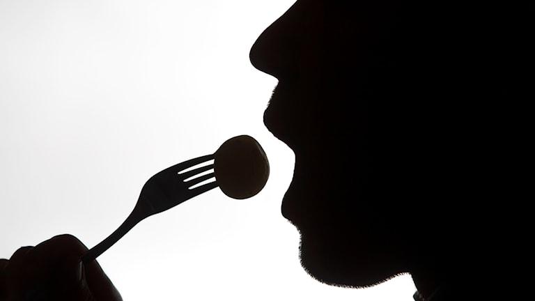 Svartvit bild i profil på person som äter mat.