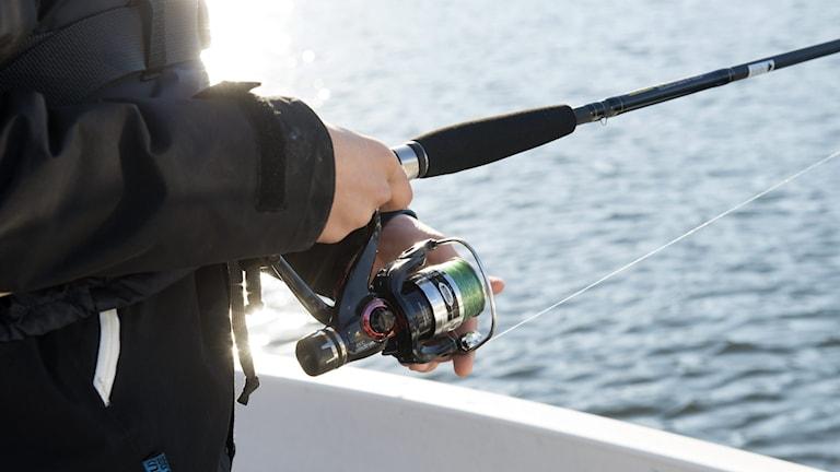 Nära bild på en person som håller i ett fiskespö.