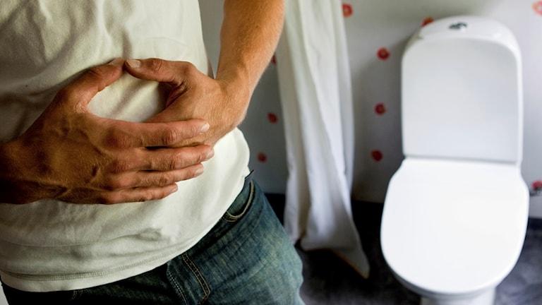 Person som håller sig för magen inne på en toalett.