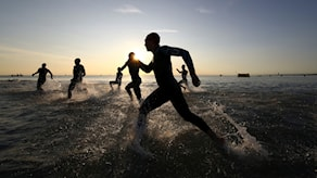 bild i motljus av triatleter som springer ut i havet för en simsträcka