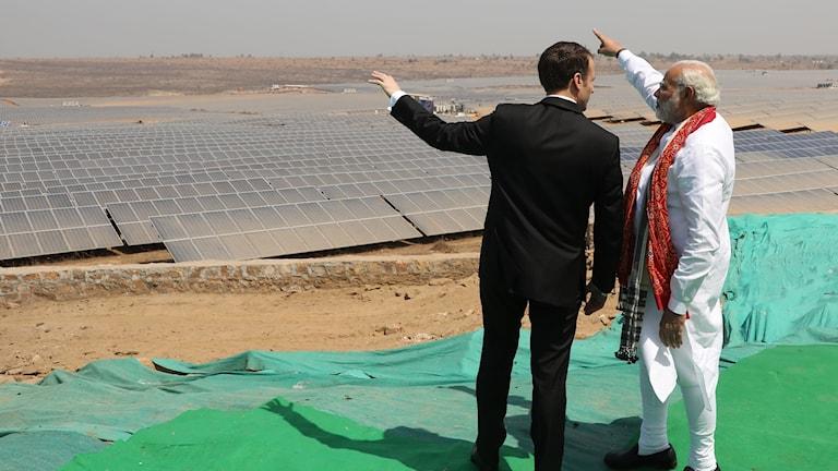 Frankrikes president Emmanuel Macron och Indiens premiärminister Narendra Modi står vända med byggen mot kameran. De pekar på en solcellspark framför sig.