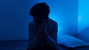 En person sitter på en säng i ett mörkt rum.