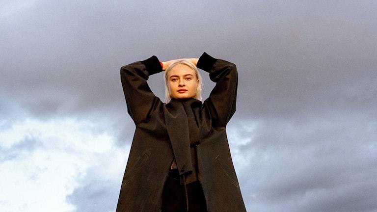 Porträtt på artisten Låpsley, ståendes med armarna över huvudet i en svart kappa.