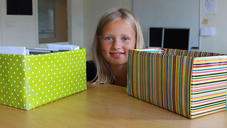Lina med två färdiga lådor att ha prylar i. Foto: Stina Ericsson/Sveriges Radio.