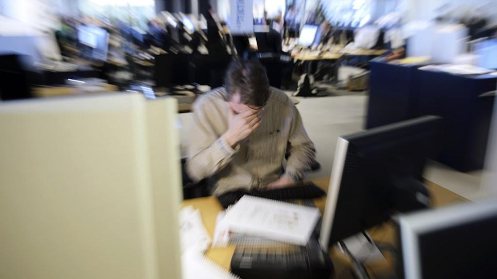 Stressad person i kontorslandskap.
