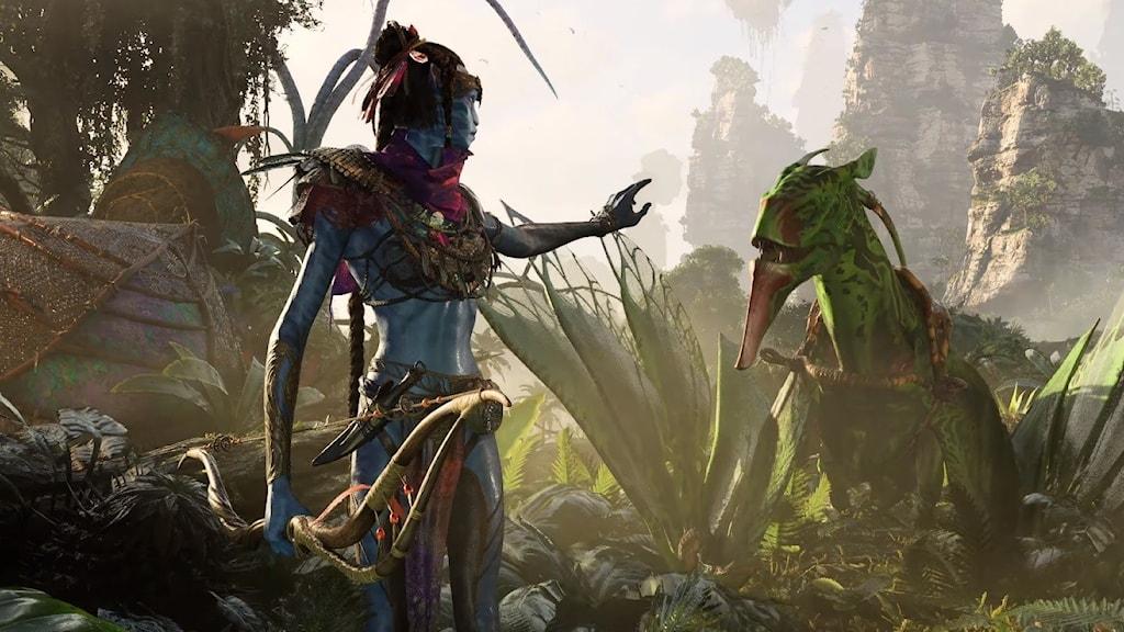 """En Na'vi från spelet """"Avatar"""" syns i naturen bredvid ett djur."""