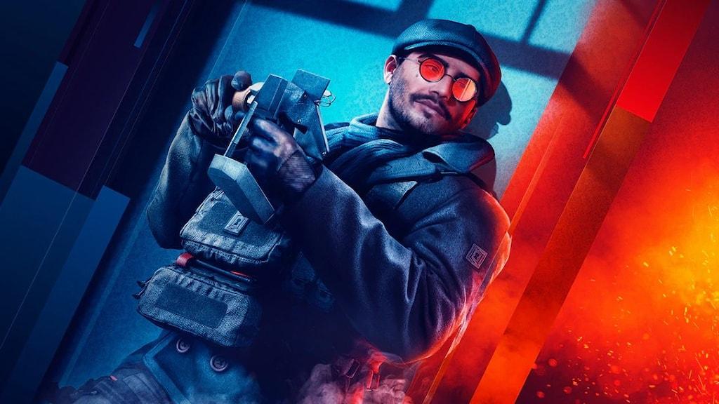 En man i solglasögon står lutad mot en vägg med ett vapen i handen.