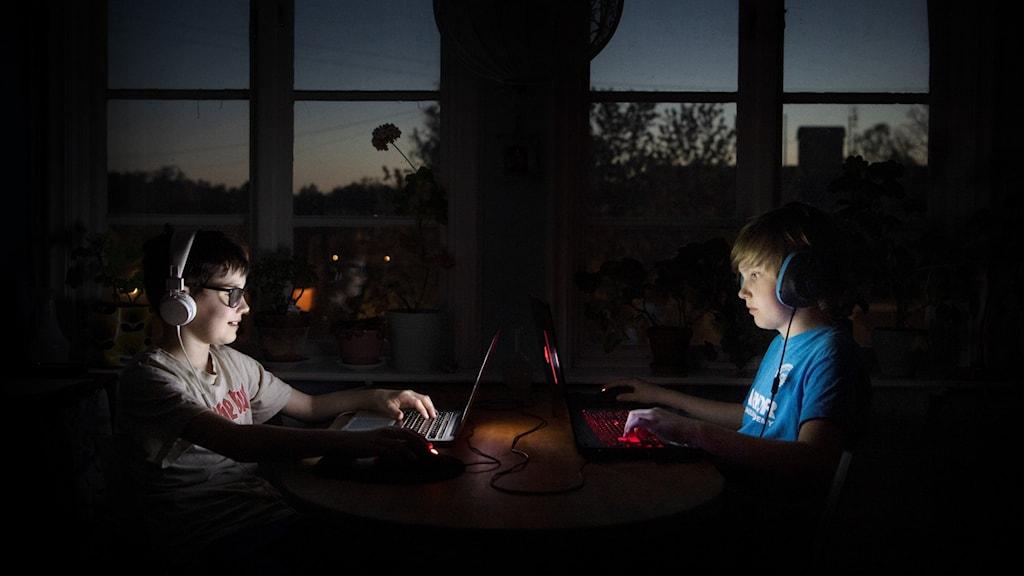 Två barn sitter mitt emot varandra och spelar Roblox och Fortnite.
