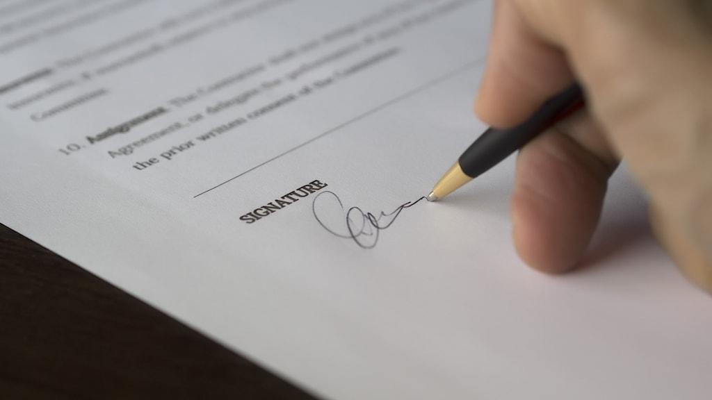 Person skriver på avtal.