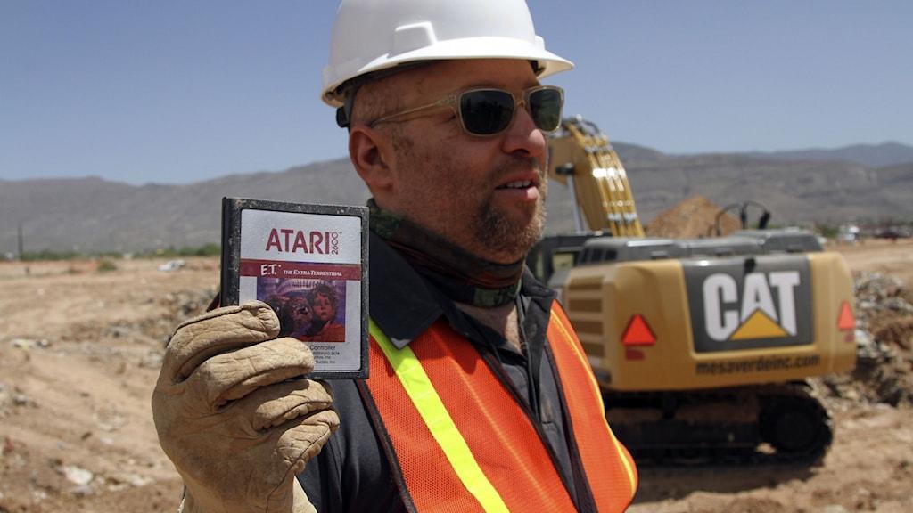 En byggarbetare håller upp retrospelet E.T. till Atari som grävts ner i en soptipp.