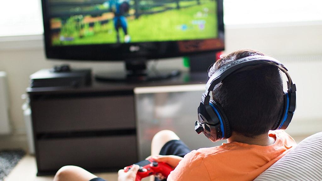 Ett barn sitter ner och spelar Fortnite på en tv.