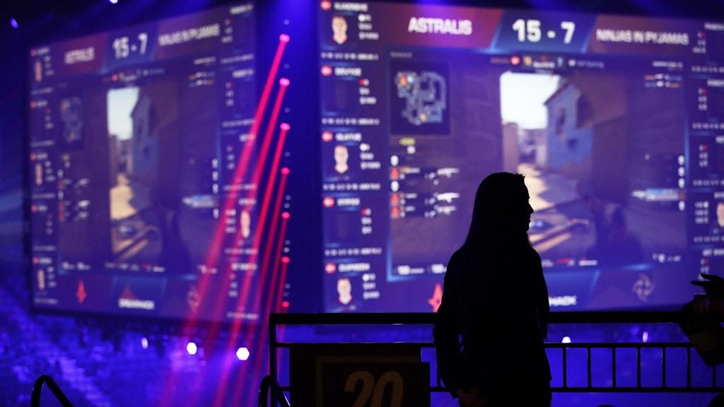 En kvinna står framför en skärm som visar en Counter-Strike-match.