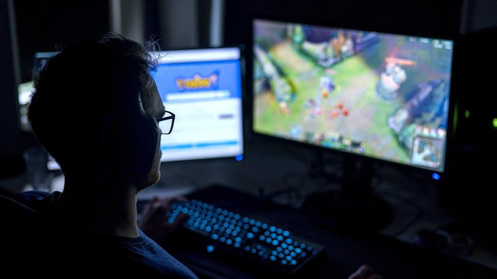 Ung man spelar datorspel i mörkt rum.