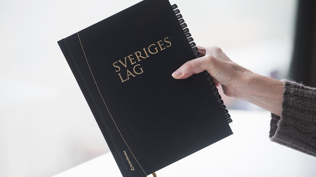 Person håller i Sveriges lagbok.