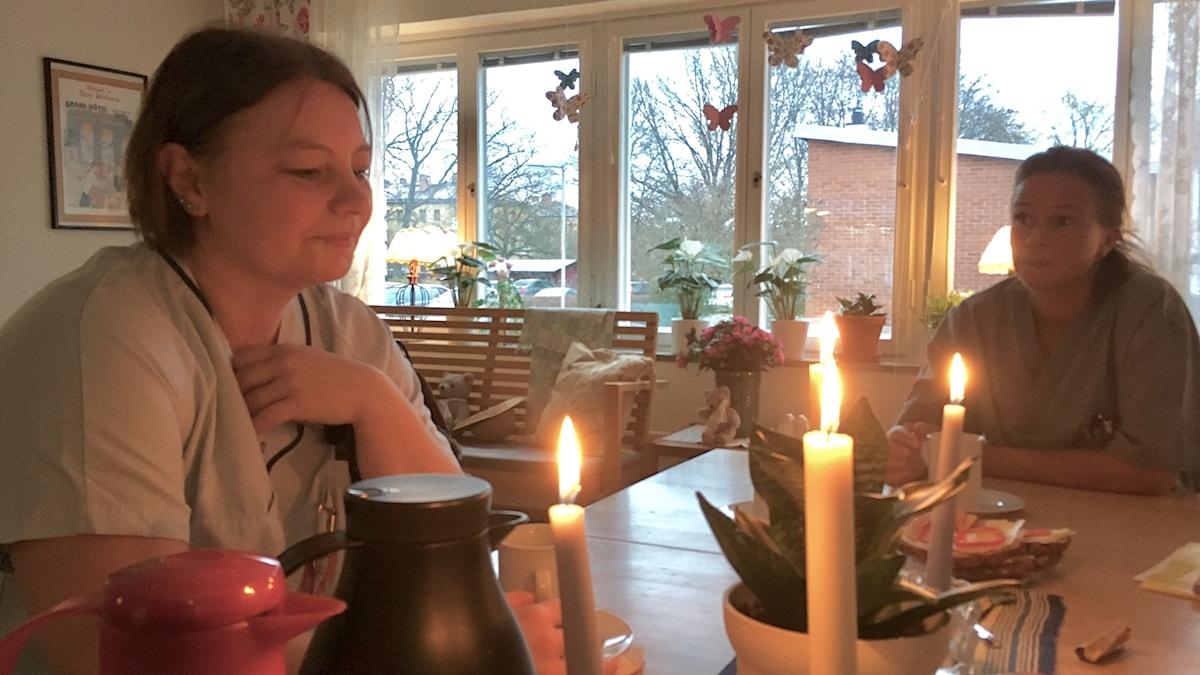 Två undersköterskor sitter vid ett bord med tända ljus och dricker kaffe.