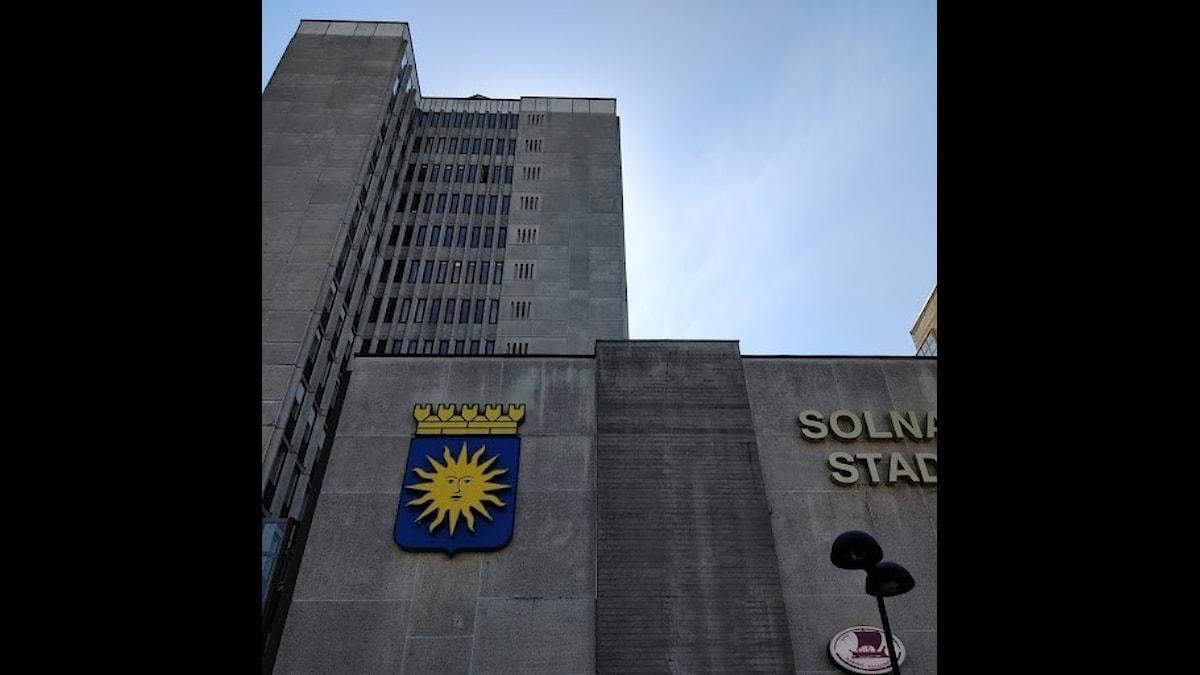 Ett stort grått betonghus med Solna kommuns vapen. På huset står det Solna Stad