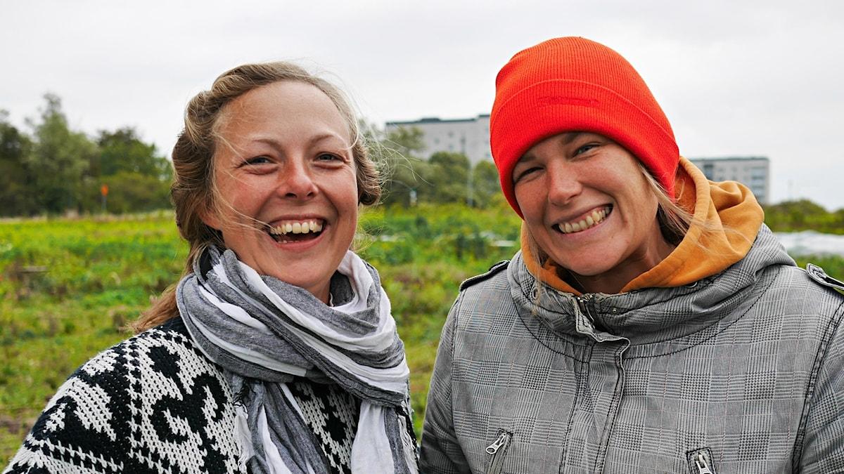 Cecilia Ward med halsduk och Monika Begtsson med en röd mössa stående på Malmö stadsodling. Båda glatt leende.