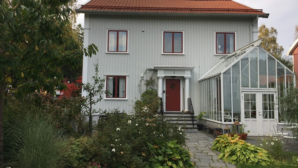 Ett grått trä hus med trädgård och växthus framför huset.