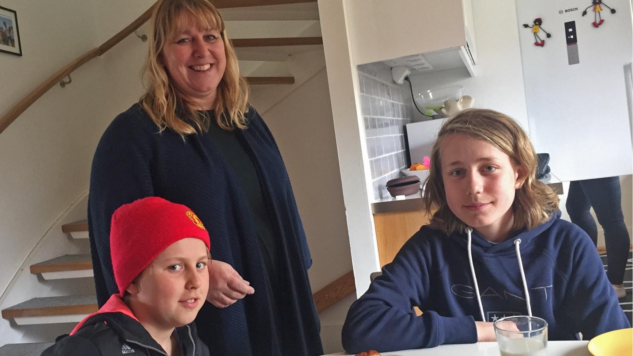 Mor och två söner i ett kök