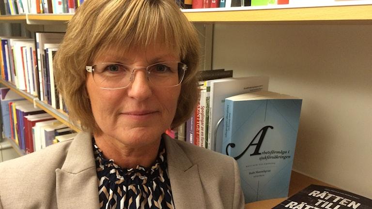 Ruth Mannelqvist framför bokhyllorna på sitt arbetsrum på Umeå Universitet.