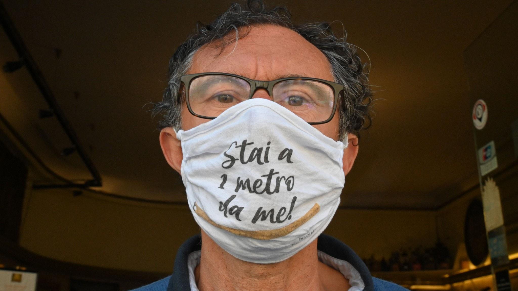 """En italiensk caféägare med ansiktsmask med texten """"håll dig en meter från mig""""."""