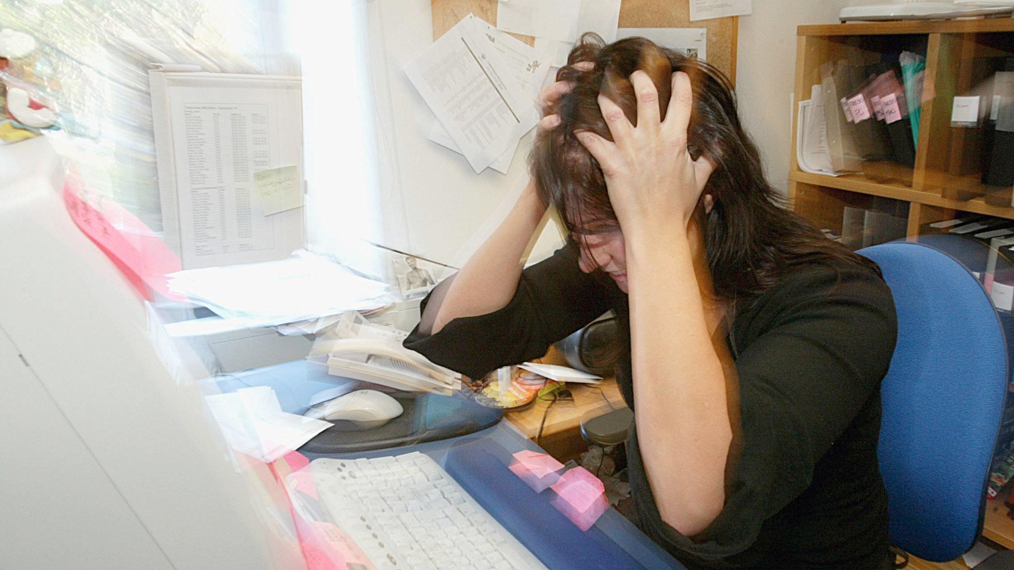 Frustrerad kvinna framför dator.