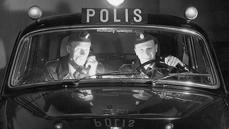 Två polismän sitter i en polisbil.